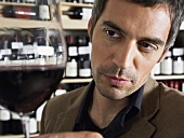 A man looking at a glass of red wine