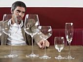 Mann sitzt mit verschiedenen leeren Weingläsern am Tisch