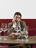 A man sitting at a table with empty wine glasses looking at his watch