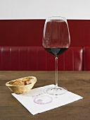 A glass of red wine on a napkin with a bread basket