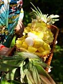 Hände halten exotischen Fruchtsalat in Holzschale