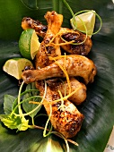 Asian chicken legs with limes on banana leaf