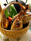 Asian chicken legs with sesame in basket; teapot