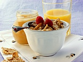 Wholemeal cornflakes with raspberries; honey jar; orange juice