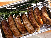 Barbecued pork sausages with rosemary in barbecue dish