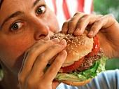 Mädchen isst saftigen Hamburger