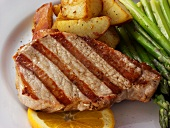 Pork steak with green asparagus, fried potatoes, orange