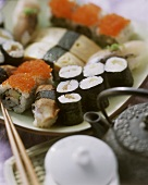 Assorted Nigiri sushi and Maki sushi; teapot
