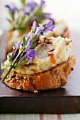 Toasted bread with white bean paste, bacon and flowers