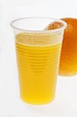 Orange juice in plastic tumbler in front of orange