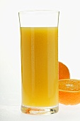 Orange juice in glass beside an orange half