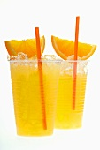 Orange juice with crushed ice, orange wedges and straw