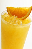 Orange juice with crushed ice and wedge of orange (close-up)