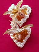 Two meringue hearts with physalis and icing sugar
