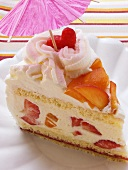 A piece of summery fruit gateau with cream; parasol