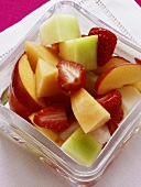 Colourful fruit salad with melon in glass bowl