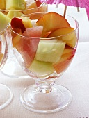 Colourful fruit salad with melon in glasses with parasol