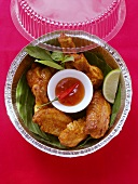 Crispy chicken wings with chili dip in lunch box