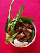 Crispy spare-ribs with herbs and krupuk in aluminium dish