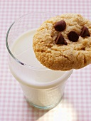 Chocolate chip cookie on a glass of milk
