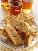 Italian almond biscuits (cantucci) on plate; Vin Santo