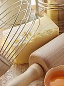 Various baking utensils, broken egg and butter