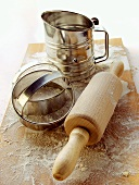 Rolling pin, cutters and flour sieve on wooden chopping board
