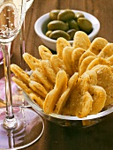 Parmesan hearts, green olives and champagne glass