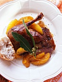 Duck with oranges, bay leaf and baguette