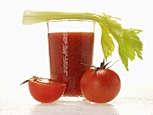 Tomato juice in glass with celery; fresh tomatoes