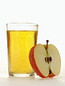 Glass of apple juice beside half an apple