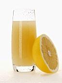 Grapefruit juice in glass beside half a grapefruit