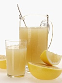 Grapefruit juice in glass and jug beside grapefruits