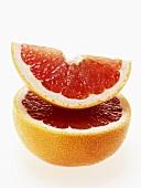 Rosa Grapefruitschnitz auf halber Grapefruit