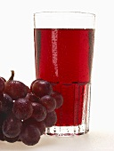 Glass of red grape juice & red grapes with drops of water