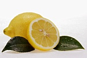 Whole and half lemon with leaves and drops of water