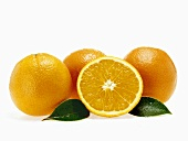 Oranges and half an orange with leaves and drops of water