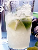 Caipirinha with ice and lime in glass; bar utensils