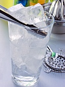 Glass with ice cubes & ice tongs in front of bar utensils