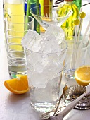 Ice cubes in glass, bar utensils, bottles & citrus fruits