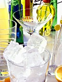 Ice cubes in glass, cocktail glasses and bottles