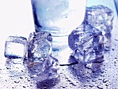 Several ice cubes in front of water glass