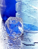 An ice cube beside a mineral water bottle
