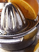 Orange on lemon squeezer with drops of water