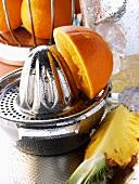 Orange on lemon squeezer, pineapple and ice cubes