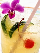 Drink with lime, ice, cocktail cherry and orchid