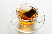 Tea in glass cup with tea bag and spoon