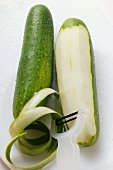 Two cucumbers with drops of water, one partly peeled