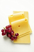 Emmental cheese in slices with red grapes