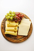 Emmental and American cheese with grapes on wooden plate